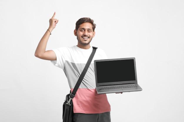 Étudiant indien montrant un écran d'ordinateur portable sur fond blanc.