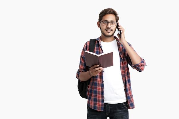 Étudiant indien parlant sur smartphone sur mur blanc