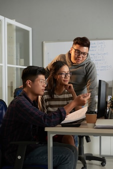 Étudiant en informatique expliquant son idée créative à des amis lorsqu'ils travaillent sur un projet de groupe