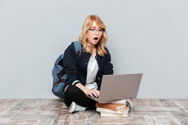 Étudiant de jeune femme choqué à l'aide d'un ordinateur portable.