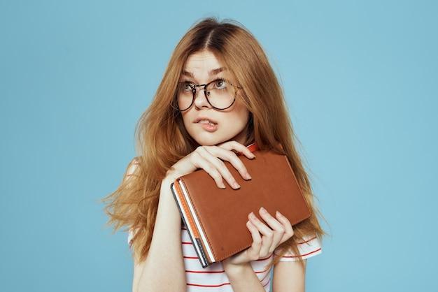 Étudiant de jeune fille avec manuel en mains