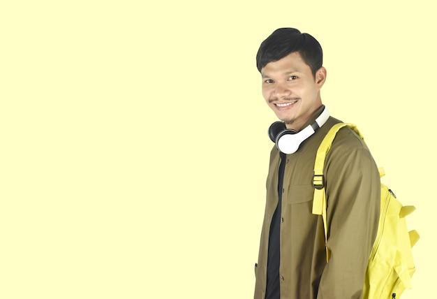Étudiant de jeune homme avec le sac à dos sur le concept de l'éducation de fond jaune