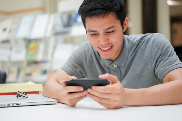 Étudiant, jouer, application jeu, sur, smartphone, après, avoir fini, lecture livre
