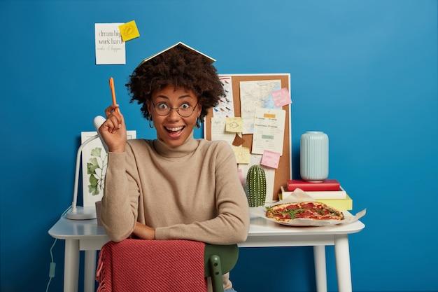 Un étudiant joyeux et bouclé écrit des notes dans son journal, garde le bloc-notes sur la tête, garde le stylo levé, porte des lunettes optiques et un pull