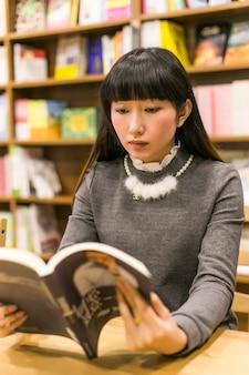 Étudiant en lisant un livre dans la bibliothèque