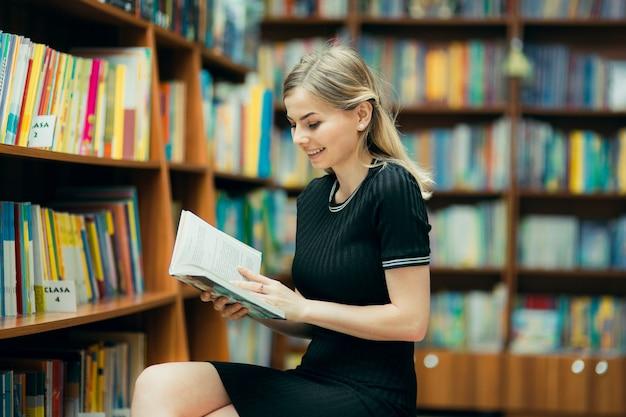 Étudiant lisant un livre dans la bibliothèque