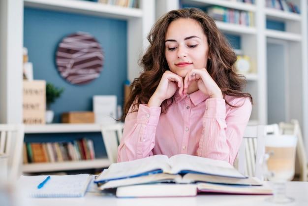 Étudiant en lisant des livres en bibliothèque