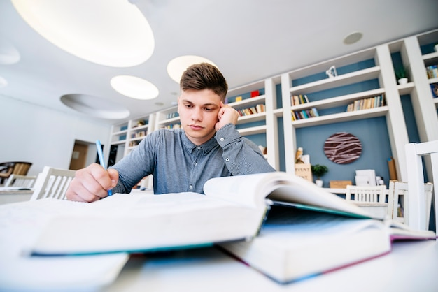 Étudiant en lisant avec des livres sur la table dans la bibliothèque