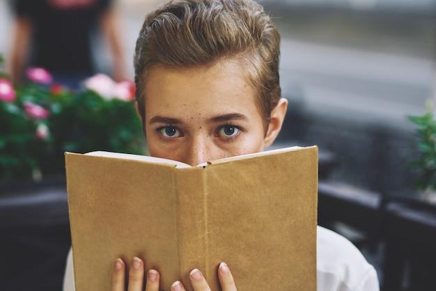 Étudiant avec un livre dans ses mains à l'extérieur reste amusant en se promenant dans l'éducation de la ville