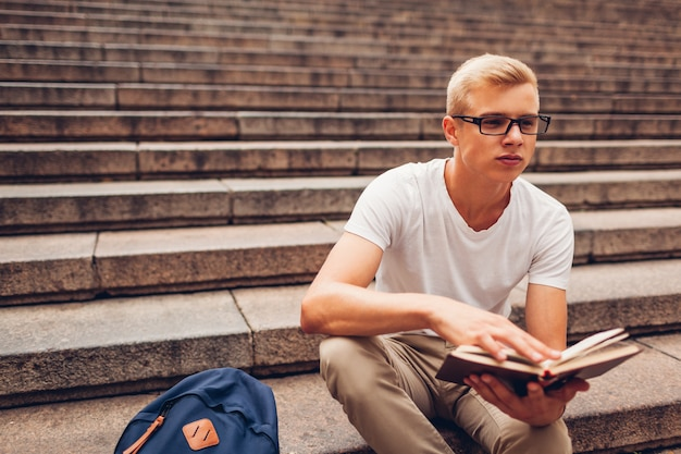 Étudiant avec livre de lecture de sac à dos assis dans les escaliers et tenant des lunettes. mec étudier dehors