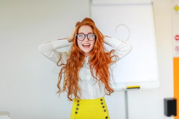 Étudiant avec des lunettes et de longs cheveux roux en classe