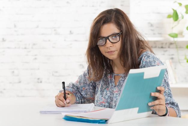 Un étudiant avec des lunettes de travail dans son bureau