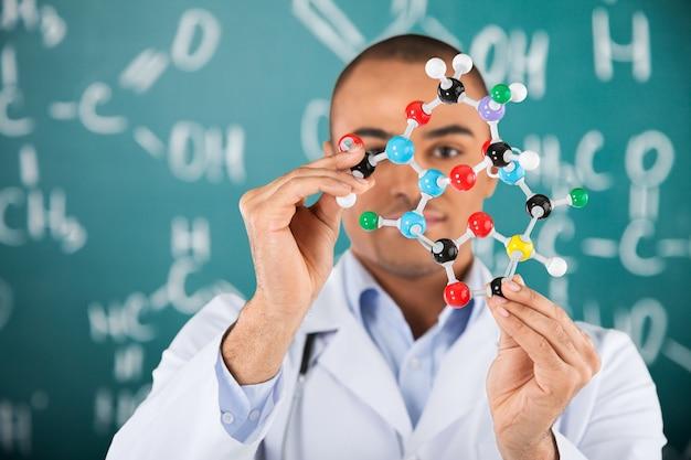 Étudiant masculin de chimie tenant la forme de molécule d'isolement sur le blanc