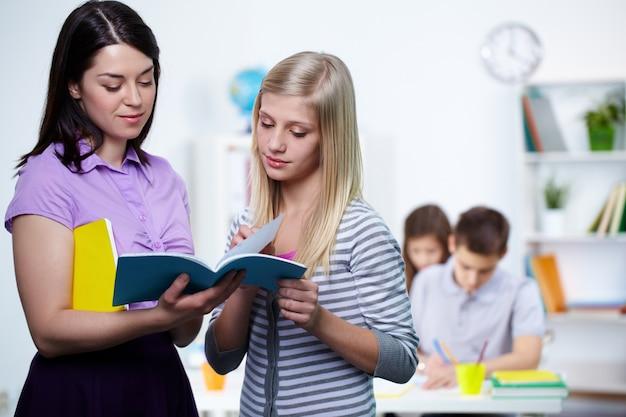 Étudiant montrant ses devoirs à l'enseignant