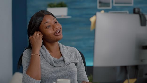 Étudiant noir discutant avec un professeur de mathématiques lors d'une conférence vidéo en ligne