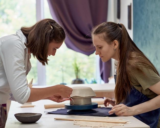 Étudiant observant le travail du maître de la modélisation d'argile avec concentration