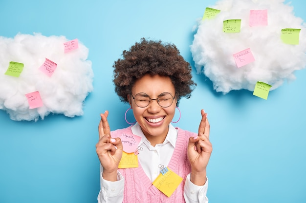 Un étudiant optimiste avec des cheveux bouclés foncés garde les doigts croisés croit en la bonne chance à l'examen porte une chemise blanche et un gilet pose contre le mur bleu