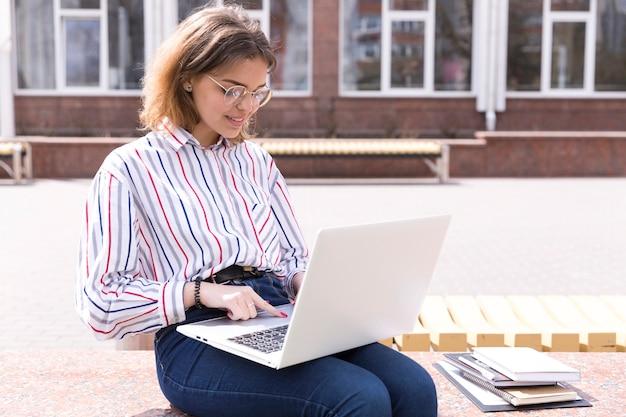 Étudiant avec ordinateur portable et cahiers