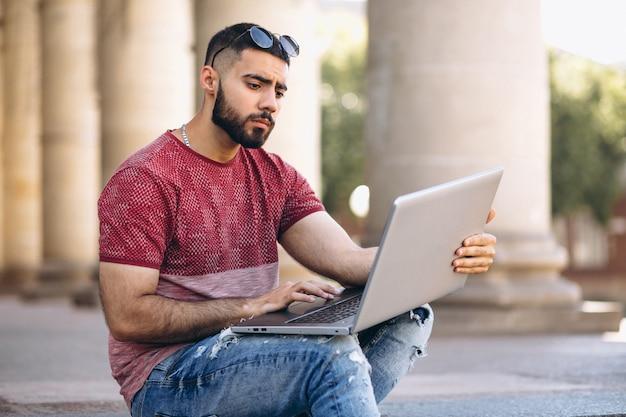Étudiant avec ordinateur portable par l'université