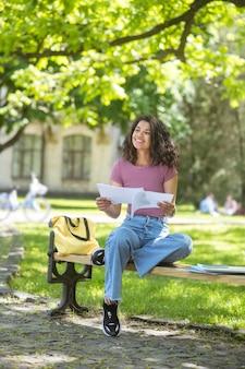 Étudiant. une photo d'une fille en t-shirt rose tenant des manuels dans ses mains