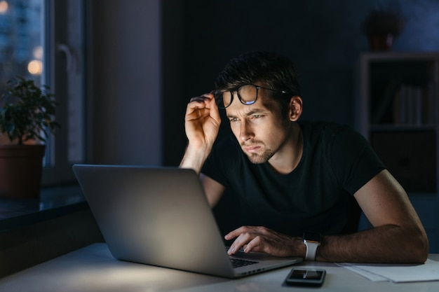 Un étudiant pigiste surmené et fatigué travaille à distance avec un ordinateur portable la nuit, tenant des lunettes sentant la fatigue oculaire