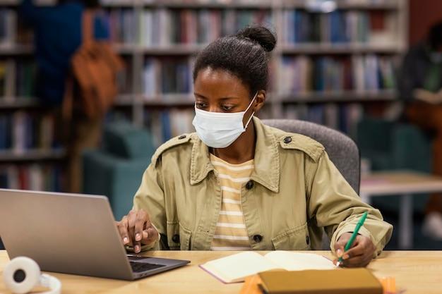 Étudiant portant un masque facial dans la bibliothèque