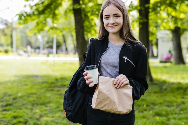 Étudiant posant avec du sac de café et de papier