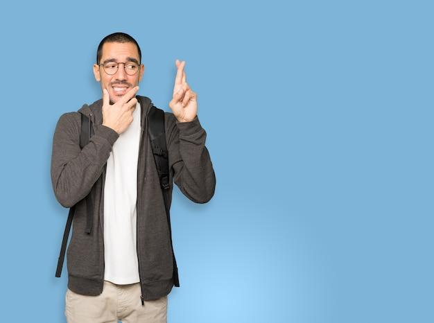 Étudiant préoccupé faisant un geste de doigts croisés