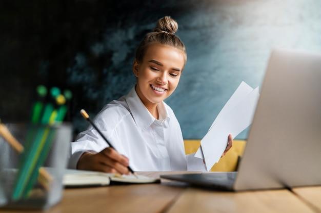 Étudiant préparant un séminaire, rédigeant des notes dans un cahier, recherchant des informations en ligne