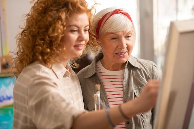 Étudiant presque talentueux. professeur d'art âgé aux cheveux gris debout près de son élève talentueux