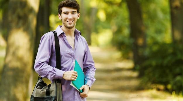 Étudiant qui réussit avec des livres dans le parc par une journée ensoleillée.