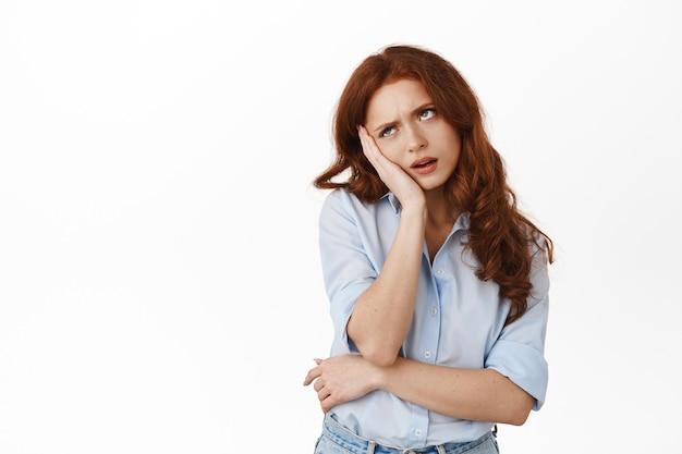 Un étudiant roux réticent ennuyé et agacé roule les yeux, se penche sur la main et se tient indifférent, assiste à une réunion ennuyeuse, se tient dérangé sur le blanc