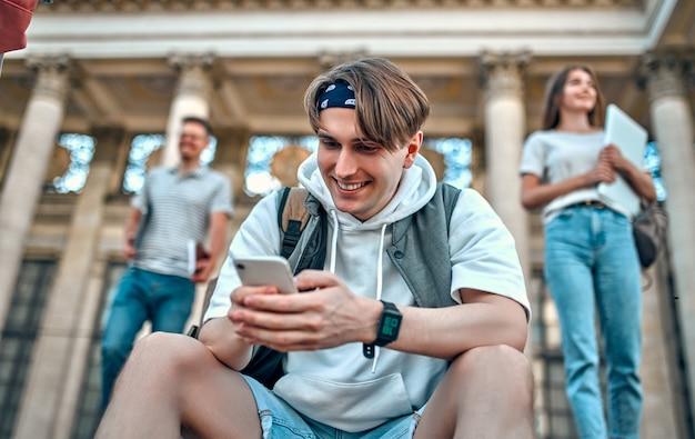 Un étudiant avec un sac à dos est assis sur les marches près du campus et utilise son smartphone