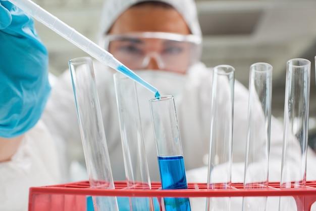 Étudiant de science protégé laissant tomber le liquide bleu dans un tube à essai