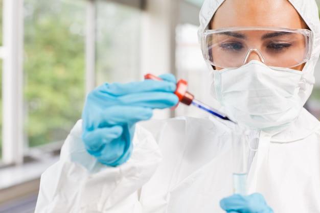 Étudiant en sciences protégé laissant tomber un liquide dans un tube à essai