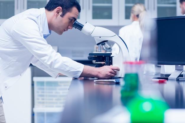 Étudiant en sciences travaillant avec un microscope dans le laboratoire