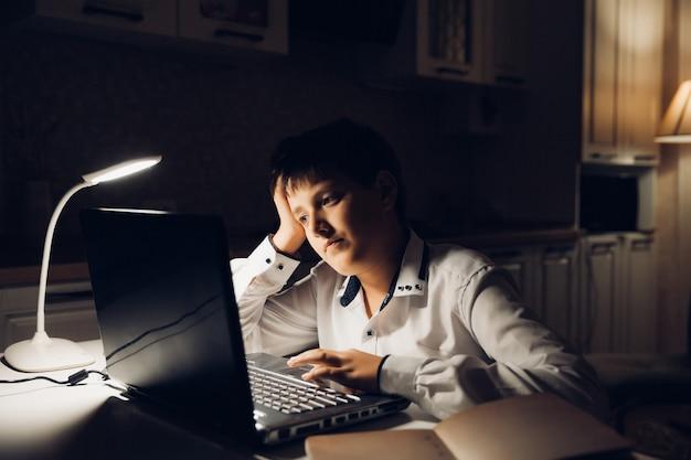 L'étudiant se prépare à l'examen tard dans la nuit. un adolescent est assis devant un ordinateur portable et s'engage tard dans la soirée.