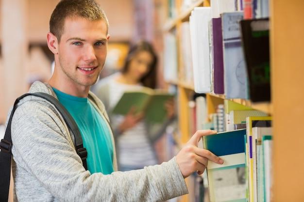 Étudiant en sélectionnant un livre de bibliothèque dans la bibliothèque