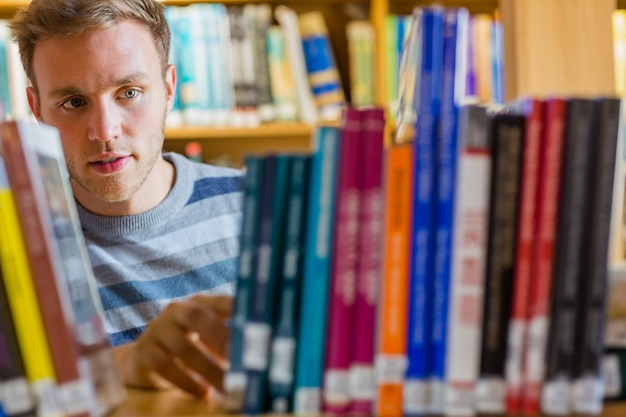 Étudiant en sélectionnant un livre dans la bibliothèque
