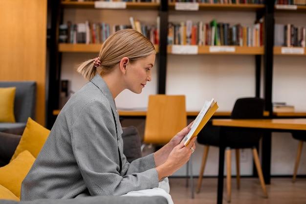 Étudiant sideview lisant à la bibliothèque