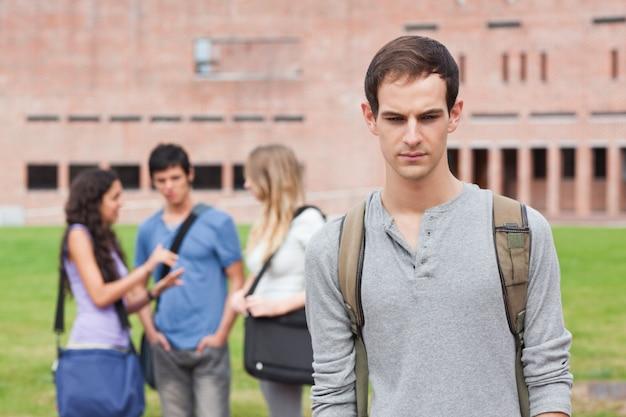 Étudiant solitaire posant pendant que ses camarades de classe parlent