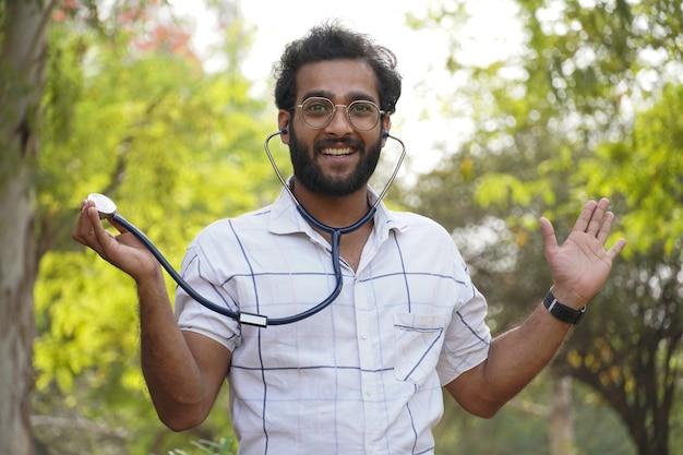 Un étudiant sorti montrant stéthoscope- étudiant avec stéthoscope et montrant le signe de réussite- concept d'éducation médicale