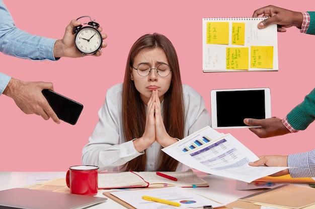 Un étudiant souhaitant garde la main dans un geste de prière, croit en la bonne fortune, ferme les yeux, prépare une tâche en économie, demande à dieu que les rêves deviennent réalité