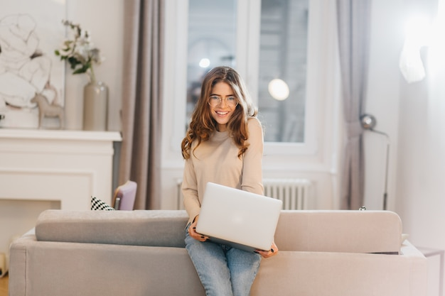 Étudiant souriant romantique dans des verres posant à la maison avec ordinateur