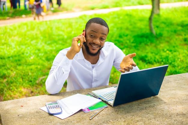 Étudiant souriant utilisant un téléphone portable à l'extérieur