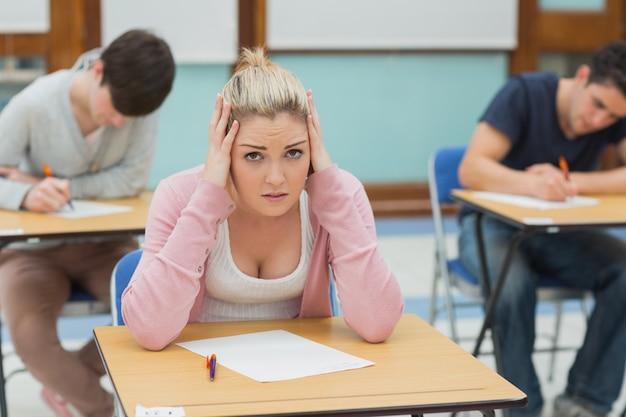 Étudiant stressé assis dans une salle de classe