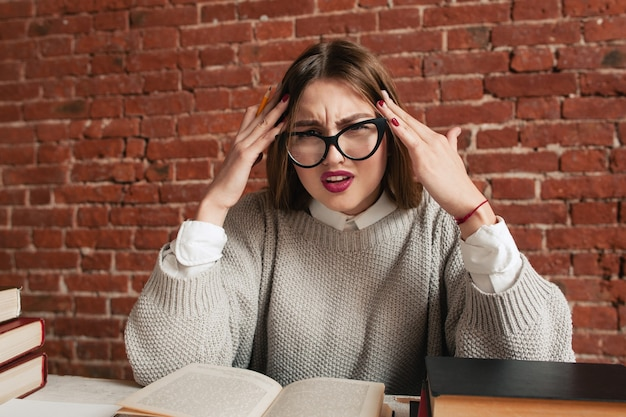 Étudiant stressé fatigué assis au bureau avec des livres