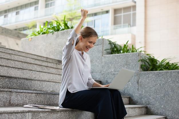 Étudiant avec succès assis avec un ordinateur portable dans les escaliers