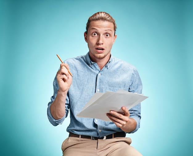 Étudiant surpris intelligent avec une excellente idée tenant des feuilles de papier