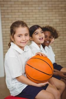 Étudiant tenant le basket-ball avec d'autres joueurs